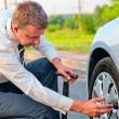 Businessman pumps car tire pump — Stock fotografie
