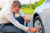 Businessman pumps car tire pump — Stock Photo