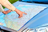 Man on the map focuses on the area — Stock Photo