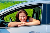 Happy female driver in her new car — ストック写真
