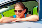 Pretty female driver in her new car — Stockfoto