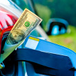Dollar bills sticking out of gas tank of a modern car — Stock Photo
