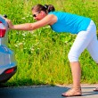 Woman pushing car out of gasoline — Stock Photo