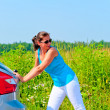 Young beautiful woman is pushing broken car on the road — Stock Photo