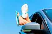 Rest in autotravel - female legs in shales in the car — Stockfoto