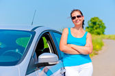 Woman standing near his car on a country road — Stock Photo