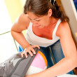 Stockfoto: Beautiful womputs inflated ball into suitcase