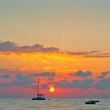 Picturesque sunset sky over the sea and the silhouettes of boats — Stock Photo