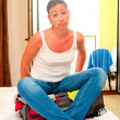 Upset girl sitting on a suitcase with clothes — Stock Photo #37303803
