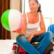 Stock Photo: Girl sitting on suitcase with inflated ball