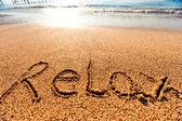 Inscriptie ontspannen op het zand van de zee — Stockfoto