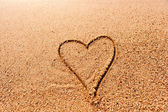 Drawing a heart on the wet sand at the sea — Stock Photo
