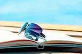 Sunglasses lying on an open book — Stockfoto