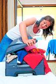 Girl collects things on the bed on holiday — Stock Photo