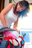 Beautiful woman puts an inflated ball into suitcase — Stock Photo