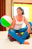 Woman sitting on a suitcase and holding a ball — Stockfoto