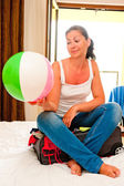 Girl sitting on a suitcase with an inflated ball — Stock Photo