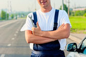 Mechanic standing beside the car with a wrench — ストック写真