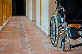 Empty wheelchair in hospital corridor — Stockfoto