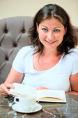Brunette reading a book at the table — Stock Photo