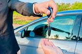 Handing over keys of new car buyer — Stock Photo