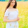 Stock Photo: Young beautiful girl in white sundress in field
