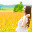 Happy womin white sundress in field — Stock Photo #38167185