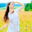 Stock Photo: Slender beautiful girl in flower field