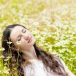 Stock Photo: Womwith closed eyes relaxes in daisies