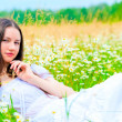 Stock Photo: Summer chamomile field and resting girl