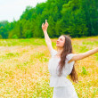 Stock Photo: Brunette with flower field with arms outstretched to sides