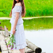 Stock Photo: Girl standing on bridge over river with bouquet