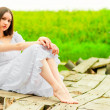 Stock Photo: Beautiful girl sits on old wooden bridge