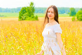 Young woman in yellow flower field — Stock Photo
