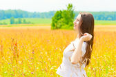 Happy woman in a white sundress in the field — Stock Photo