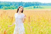 Charming brunette in a field of yellow flowers — 图库照片