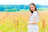 Portrait of a smiling brunette in the field — Stock Photo