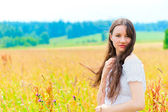 Young beautiful woman with long hair in white in colors — 图库照片