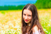 Portrait of a young beautiful girl in camomile field — Stok fotoğraf