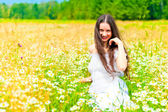 Smiling girl in camomile field rests — 图库照片