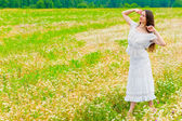Young brunette woman walking in a field with daisies — Stock Photo