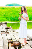 Girl on an old wooden bridge with a bouquet of flowers — Stock Photo