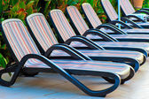 Number of empty sunbeds around the pool at the hotel — Stock Photo