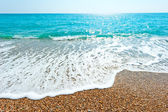 Glare of the sun and the sea foamy wave — Stock Photo