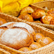 Wicker basket full of bread and rolls — Stock Photo