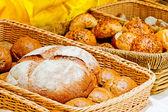 Cesta de mimbre llena de pan y rollos — Foto de Stock
