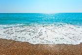 Foamy wave rolls on a sandy beach — Stock Photo
