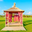 Gazebo with a thatched roof on a green lawn — Stock Photo
