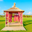 Stock Photo: Gazebo with a thatched roof on a green lawn
