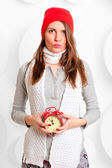 Girl in a hat and scarf with red alarm clock — Photo